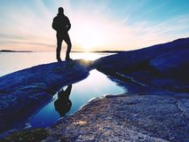 Lange wandelaar in donkere sportkleding met rugzaktribunes op klip boven overzees De mens geniet van verbazend zonsondergang Stock Foto