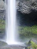 Lange waterval in pool van water met rotsoverhangend gedeelte op achtergrond Stock Foto's