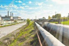 Lange weg op de industriezone dichtbij de chemische installatie De aard probeert zich daar tegen te verzetten stock afbeeldingen