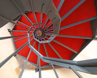 Lange Wendeltreppe mit rotem Teppich Stockfotos