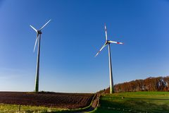 Lange windturbines op scène van het plattelands de landelijke landschap met koe Stock Afbeelding