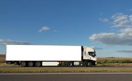 Lange witte vrachtwagen op weg Stock Afbeeldingen