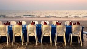 Langer Abendtisch und Stuhl neben dem Sand setzen auf den Strand Lizenzfreies Stockfoto
