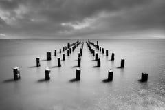 Langer alter hölzerner Pierbrückenumfang von Strand zu Meer Tiefer bewölkter Himmel nach dem großen Sturm Erwartung zu den Erfolg stockfotos