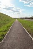 Langer Asphaltweg nahe bei grünem Hügel am sonnigen Frühlingstag Stockfotografie