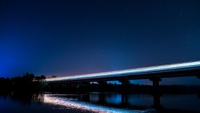Langer Belichtungsschuß des Zugs auf Brücke nachts lizenzfreie stockfotografie