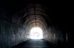 Langer dunkler Tunnel mit Leuchte am Ende Stockfoto