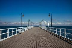 Langer hölzerner Pier mit Laternen und weißen Sperren Stockfotografie