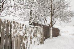 Langer hölzerner Winterzaun und elektrischer Pfosten in der guten Perspektive Stockfotografie