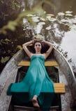 Langer Haar Brunette in einem Kleid, das auf dem Boot liegt Stockfotos