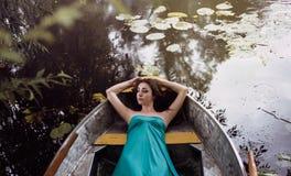 Langer Haar Brunette in einem Kleid, das auf dem Boot liegt Stockbilder