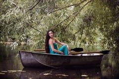 Langer Haar Brunette in einem Kleid, das auf dem Boot sitzt Lizenzfreie Stockfotografie