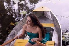 Langer Haar Brunette in einem Kleid, das auf dem Boot sitzt Lizenzfreies Stockfoto