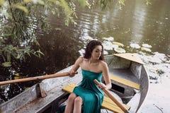 Langer Haar Brunette in einem Kleid, das auf dem Boot sitzt Stockbilder