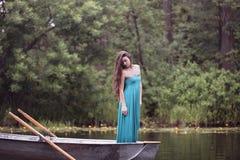 Langer Haar Brunette in einem Kleid, das auf dem Boot steht Stockfotos