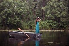 Langer Haar Brunette in einem Kleid, das auf dem Boot steht Stockbild