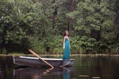 Langer Haar Brunette in einem Kleid, das auf dem Boot steht Stockfotografie