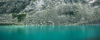 Langer horizontaler Foto Steindamm auf dem Ufer von einem Gebirgssee Stockbild