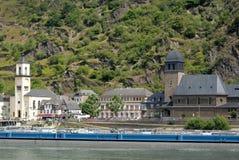 Langer Lastkahn und ein kleines Dorf mit zwei Kirchen auf den Banken des Rheins in Deutschland Lizenzfreie Stockfotos
