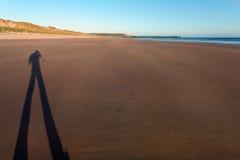 Langer mit Beinen versehener Schatten auf einem sandigen Strand bei Sonnenuntergang Stockfotos