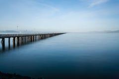 Langer Pier, der heraus in das Wasser ausdehnt Stockfoto