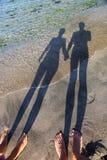 Langer Schatten der Paarholdinghände Stockfotos