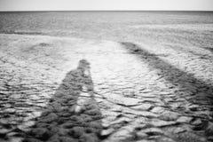 Langer Schatten des Mannes, der Foto von auf einem Sandstrand mit unscharfem Meer im Hintergrund, trauriges Konzept, einsames Kon Stockfotos