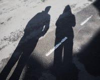 Langer Schatten des Mannes und der Frau auf Asphaltstraße mit Trennungslinie draußen lizenzfreies stockfoto