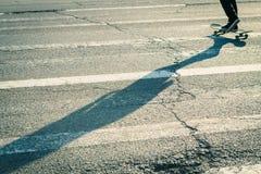 Langer Schatten eines Skateboardfahrers, der durch Zebrastreifen kreuzt Stockbilder