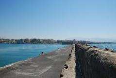 Langer Steinpier, der in das blaue Meer ausdehnt stockfotos