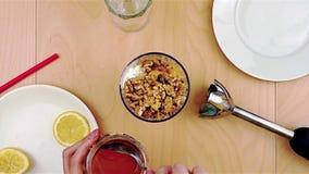 Langere gietende honing over okkernoten in de mixer voor een gezonde en voedzame smoothie stock videobeelden