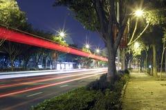 Langes Belichtungsbild von den Autos, die über einer Straße hetzen Stockfoto