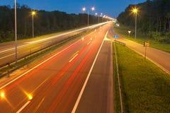 Langes Belichtungsfoto auf einer Landstraße mit hellen Spuren Lizenzfreie Stockfotos