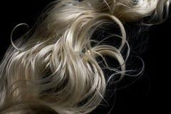 Langes blondes Haar auf schwarzem Hintergrund Stockfoto