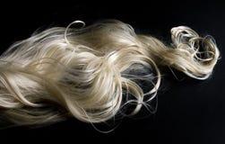 Langes blondes Haar auf schwarzem Hintergrund Stockbild
