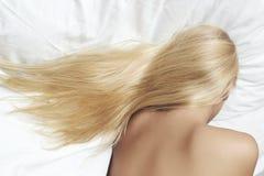 Langes blondes Haar. schöne blonde Frau, die im Bett schläft Lizenzfreie Stockbilder