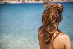 Langes blondes rotes Haarmädchen, das in dem Meer mit einem überreichung h aufpasst lizenzfreie stockfotografie