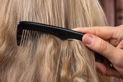 Langes blondes weibliches Haar kämmen - nahes hohes Stockbilder