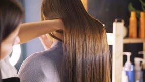 Langes dunkles Haar eines jungen Mädchens Gl?nzendes und seidiges Haar nachdem dem Keratingeraderichten Der Effekt des Keratins,  stock video