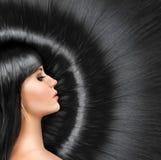 Langes glänzendes Haar eines schönen Brunette Stockbild