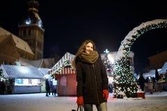 Langes Haarmädchen auf europäischem Weihnachtsmarkt Junge Frau, die Winterurlaub-Jahreszeit genießt Unscharfer Lichthintergrund,  Stockbilder