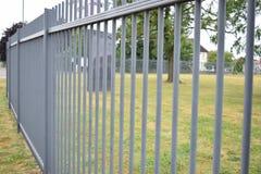 Langes metallisches Tor außerhalb eines grasartigen Feldes Lizenzfreies Stockfoto