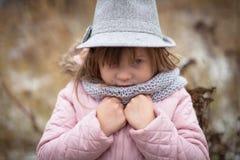 Langes rauhaariges Mädchen in der Jacke, im grauen Schal und im Fedorahut Lizenzfreies Stockfoto