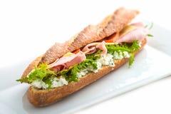 Langes Sandwich mit Schinken, Käse, Tomaten und Kopfsalat Getrennt auf weißem Hintergrund Lizenzfreies Stockfoto