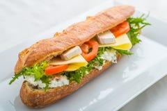 Langes Stangenbrot mit Tofu, Käse, Tomaten und Kopfsalat auf weißer Platte Stockbilder