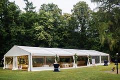 Langes weißes Zelt für Hochzeitsfest im Wald Stockbild