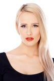 Langhaarige blonde Frau, die auf Weiß aufwirft Stockfotos