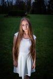 Langhaarige blonde Frau im weißen Kleid nachts im Stadtpark Lizenzfreie Stockbilder