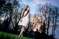 Langhaarige blonde Frau im weißen Kleid nachts im Stadtpark Stockfoto
