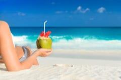Langhaarige Blondine mit Blume im Haar im Bikini auf tropischem Strand Stockfotos